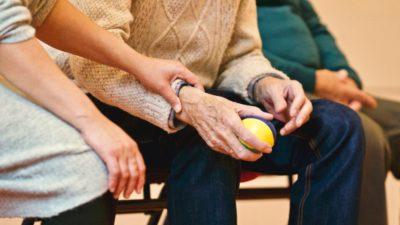 Frau hält älterem Mann die Hand