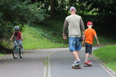 Mann und Kind fahren Skateboard im Park