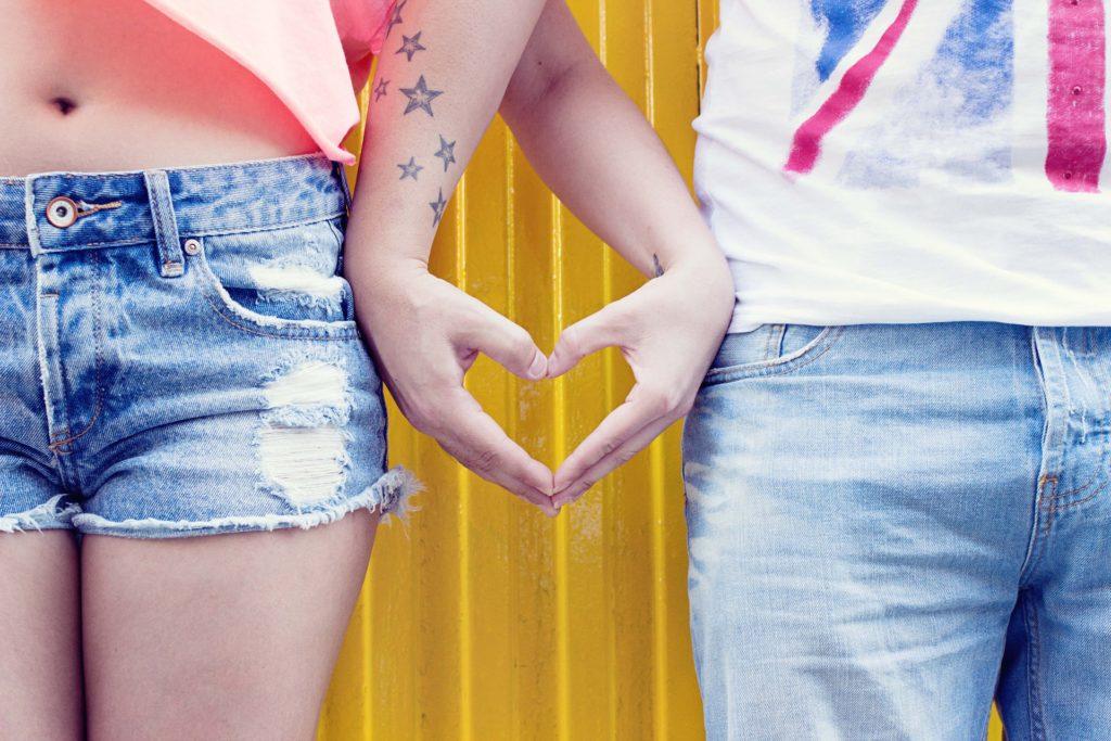 Zwei Jugendliche halten Hände und formen ein Herz